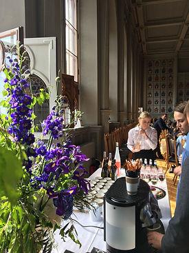 Naistarjoilija kaataa roseeviiniä laseihin kauniissa juhlasalissa Helsingissä kesäpäivänä.