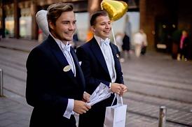 Kaksi hymyilevää miestarjoilijaa vastaanottavat juhlaväkeä kadulla Helsingissä.