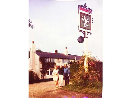 Julie and Johnny Stokes with Friend near Pub sign