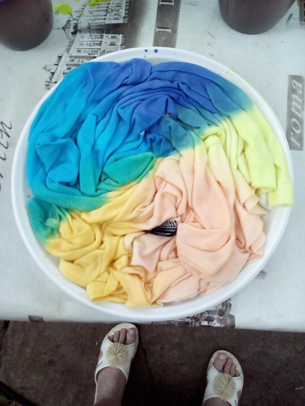 футболка, закрученная спиралью, окрашивается несколькими цветами,потом сохнет.