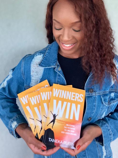 Taneka Rubin holding book Winners Win - Youth Sponsorship