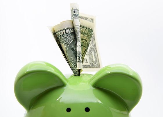 Green piggy bank with US dollar bills on