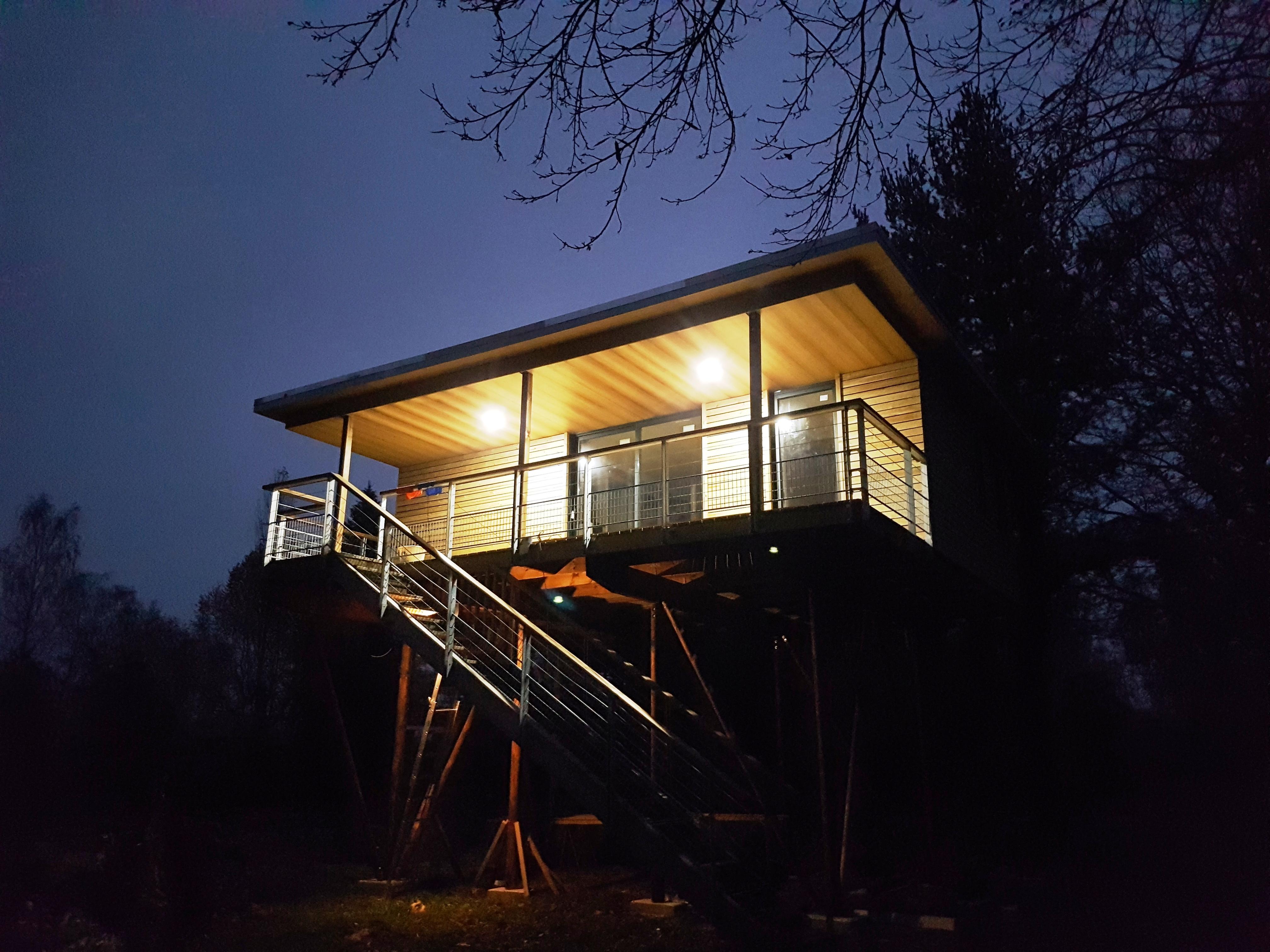 vue de nuit maison dans les arbres