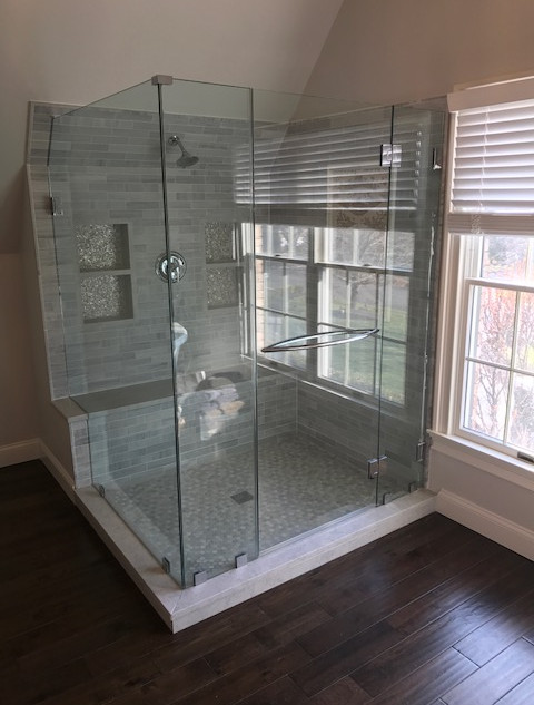 90 degree glass to glass hinges with crescent towel bar on door and mitered corners.