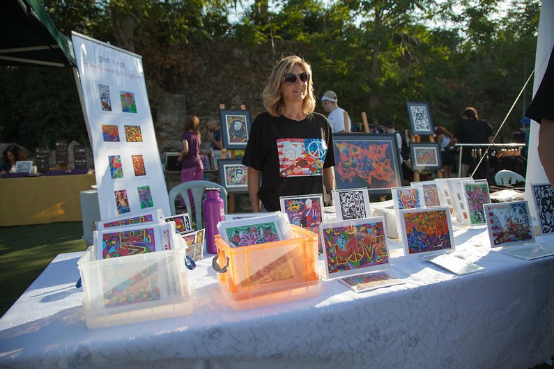 Marina Shear manning the booth featuring Glen Shear's artwork at the Jerusalem Woodstock Revival