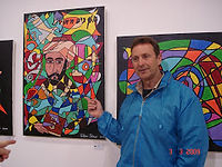 Chaim Wigoda pointing to a portrait of the Rambam at Glen Shear's Art Exhibition