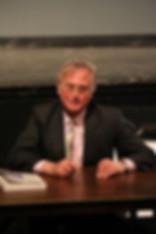 Richard Dawkins sitzt am Tisch