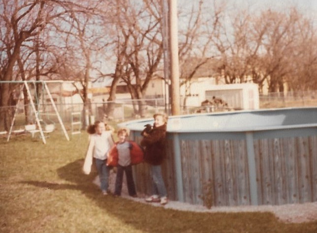 Our suburban backyard as kids. My sister is holding our pet rabbit.
