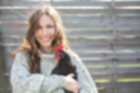Happy young woman holding his chicken in the backyard.jpg