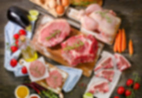 Different types of fresh raw meat with vegetables and herbs on wooden table.jpg