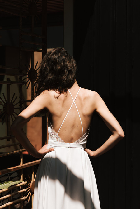 """With its american harmhole and fine crossed back straps, Héloïse is charismatic. The top is covered with a unique tulle. The slit skirt subtly reveals the legs hidden behind the crêpe. The dress has something of """"je ne sais quoi"""" with the removable Julie shirred tulle overskirt for a fine volume."""