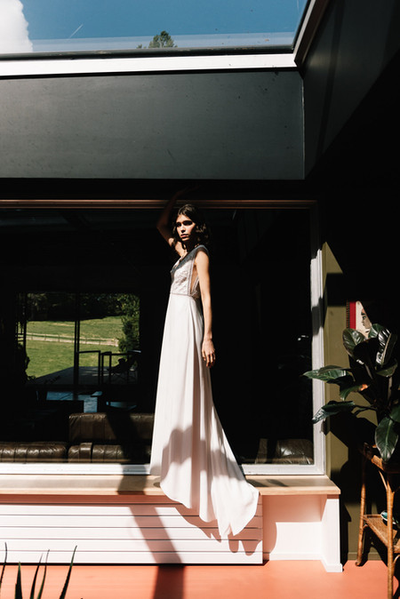 Violette is a summery dress made of a straight crepe skirt and of a guipure deep V neckline in the front and back. A sheer tulle cutout on the sides is lined with a jour-échelle braid as a highly graphic detail.