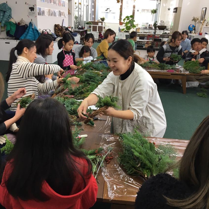 Yukako-san showing how to wrap the evergreen around the wreath base.