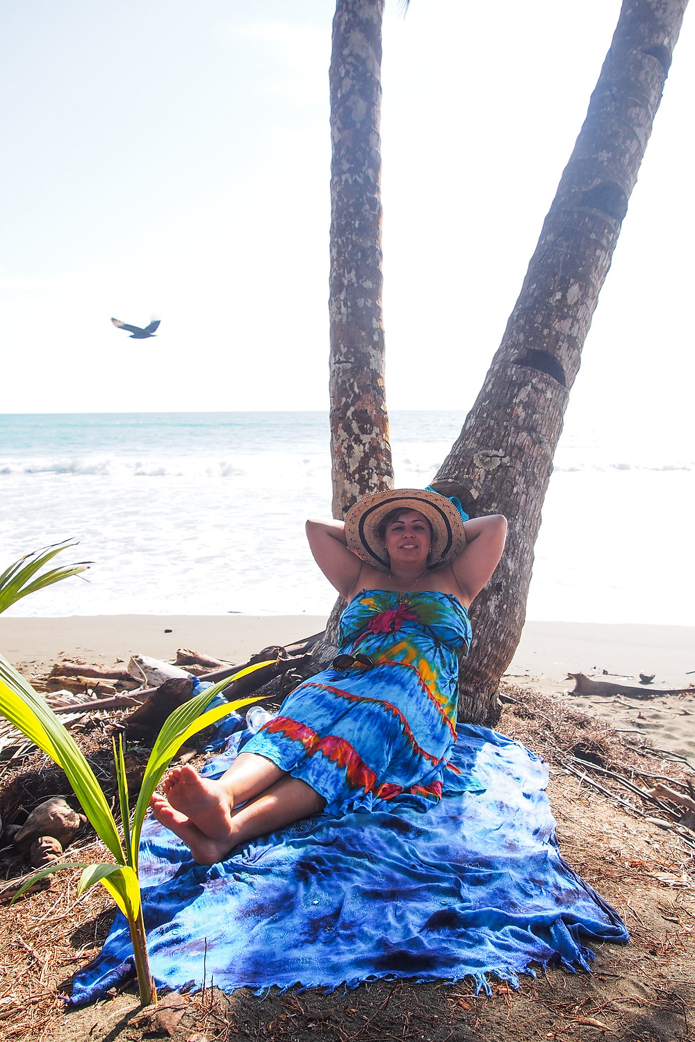 Devina Kaur on the beach sitting under a palm tree wearing a blue striped dress