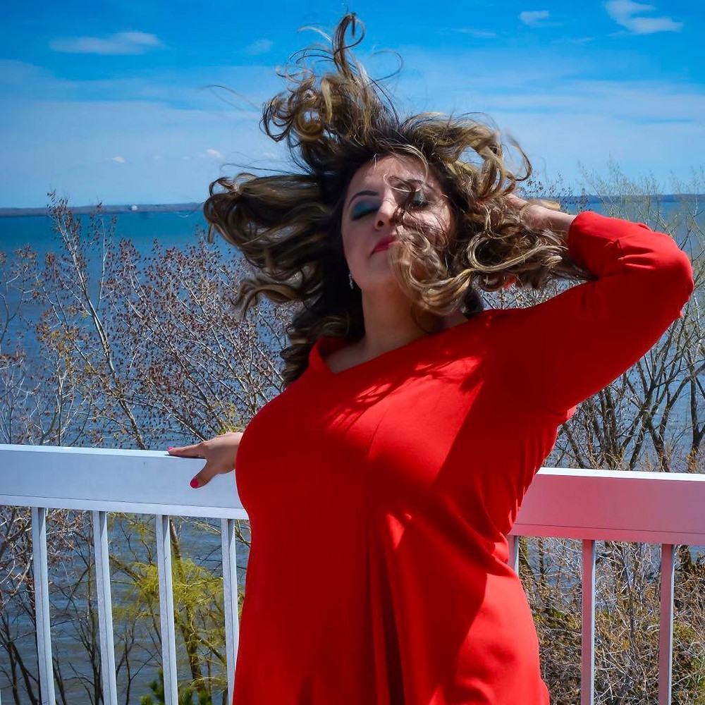 Devina Kaur wearing a red dress, wind blowing through her hair