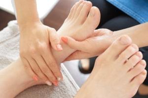 資格を取得して高齢者に足のむくみをマッサージする介護リハビリセラピスト