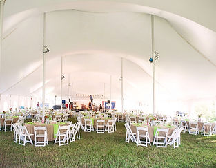 Wyoming Tent wedding with tables chairs linens beautiful  flowers add color for the recepetion.