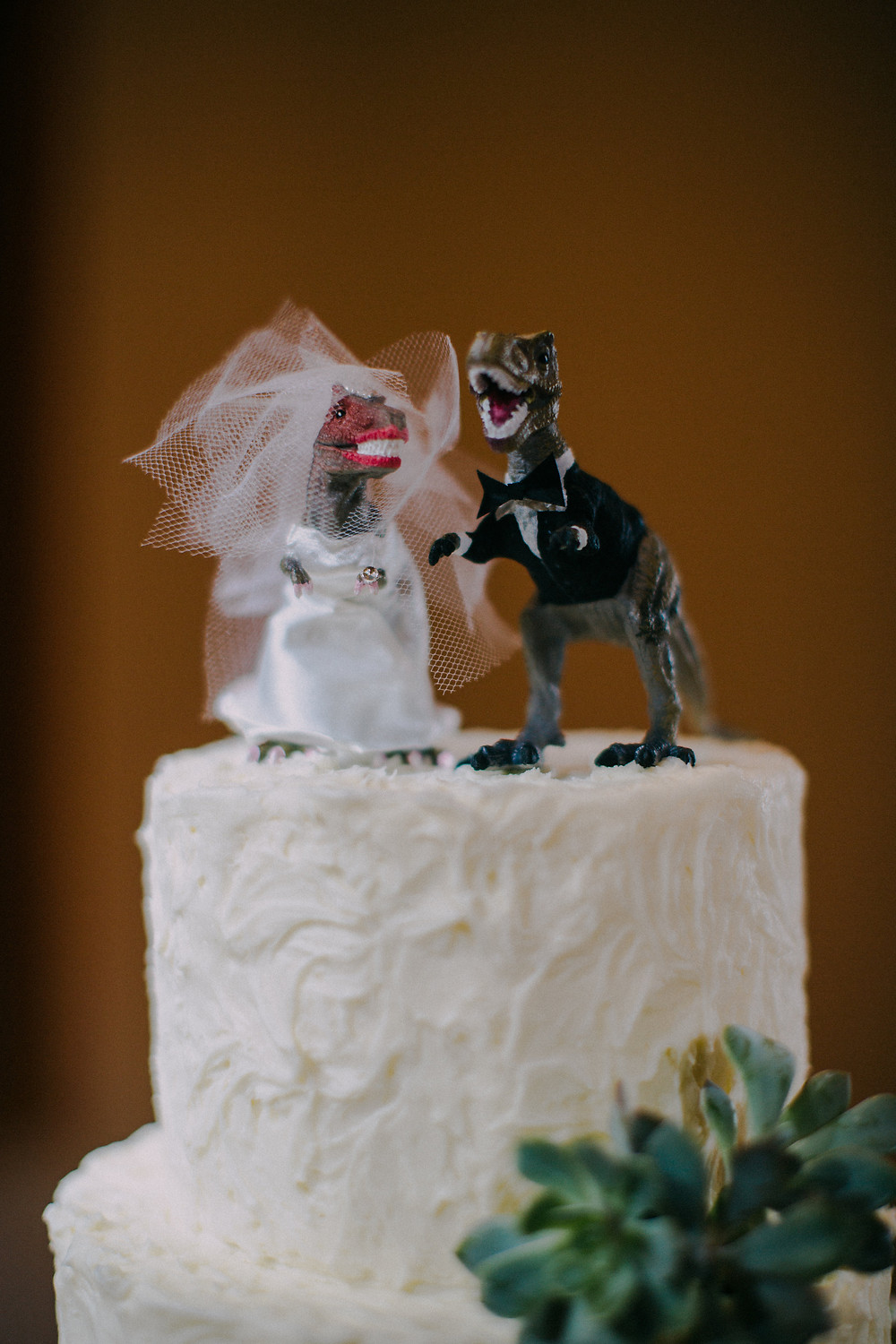 T-rex Wedding Cake Topper on White Wedding Cake with Succulents