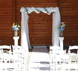 White garden chairs line the aisle to a gazebo draped in flowing fabric. Amphitheater in Cheyenne Wyoming wedding