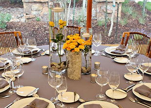 Charcoal majestic tablecloth and napkins offer a neutral backdrop for beautful yellow spray roses. Saratoga Wyoming wedding. Wyoming wedding rental