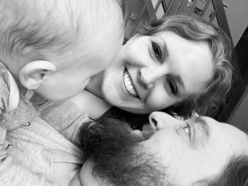 Black and white photo of Cassie in between her husband and her daughter. Cassie is looking at the camera, her husband is looking at her, and their baby - whose face is away from the camera - is also looking at Cassie.