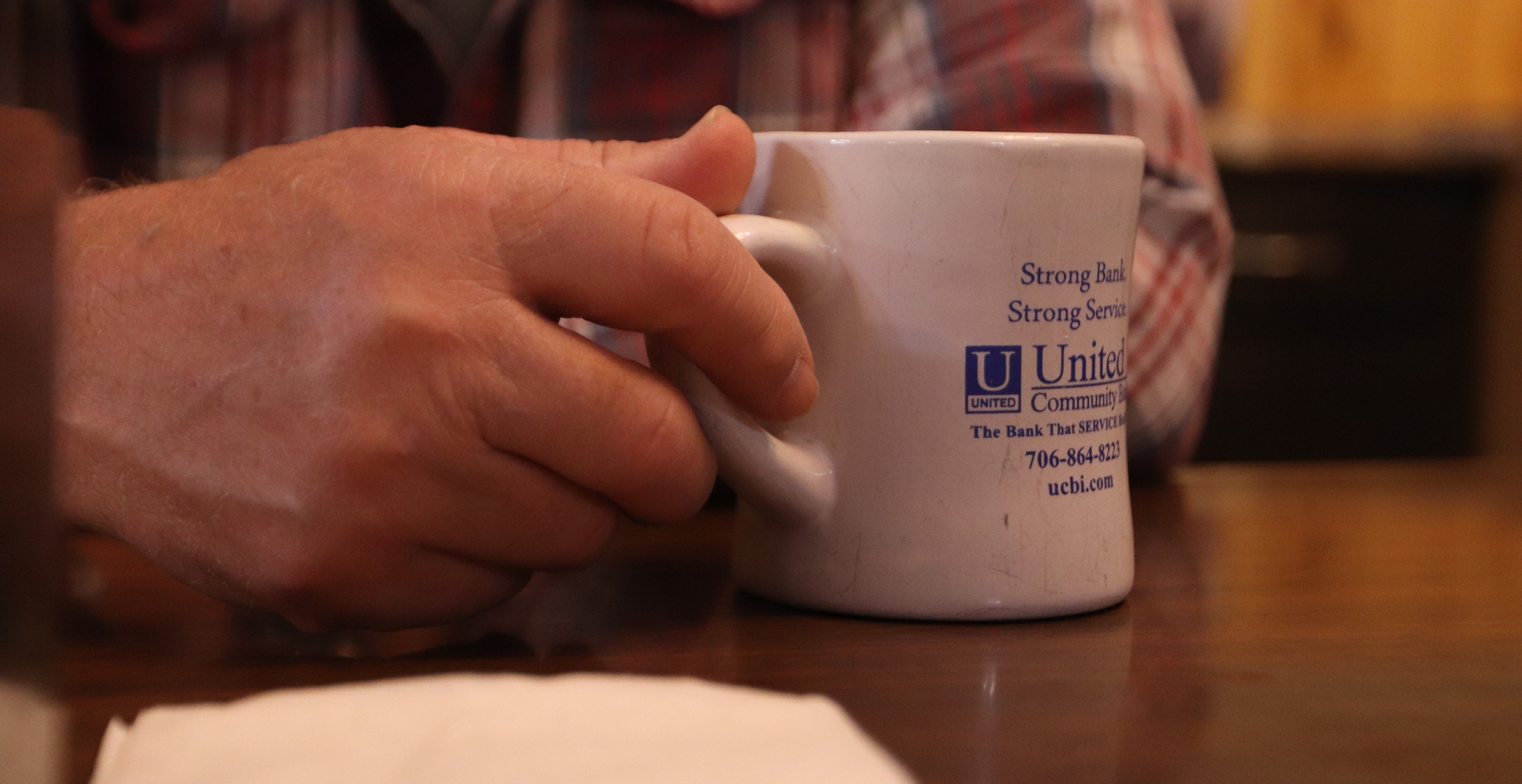 Tommy Tanner, 67, holds his coffee cup on Saturday, March 30, 2019 in Dahlonega, Georgia. Tanner drinks several cups of coffee each morning just like every other member at the table. (Photo/Tristen T. Webb)