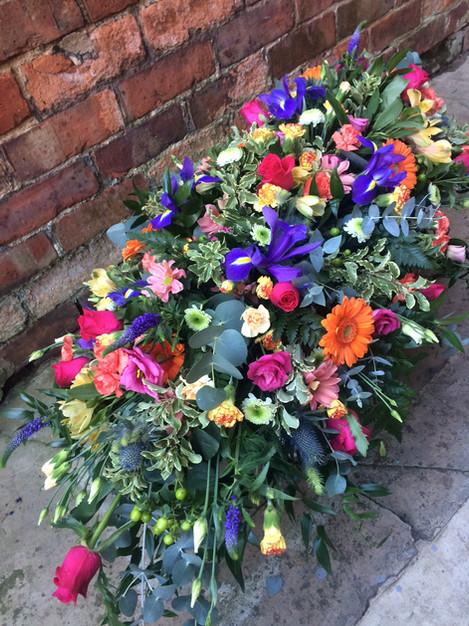 Vibrant casket spray (from £170)