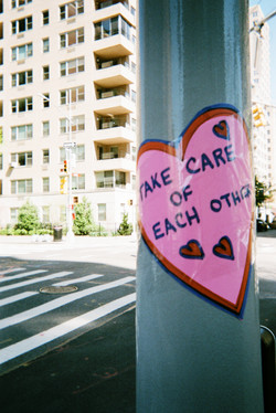 """Heart-shaped """"Take Care of Each Other"""" sign"""