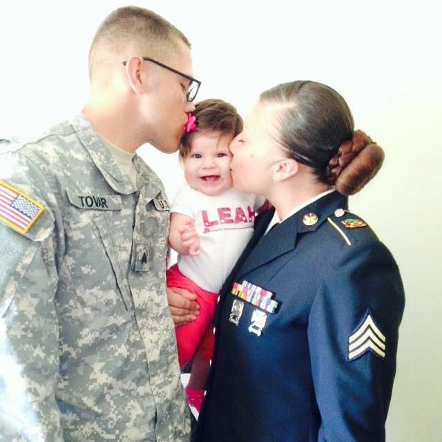 Military parents in uniform kissing their baby