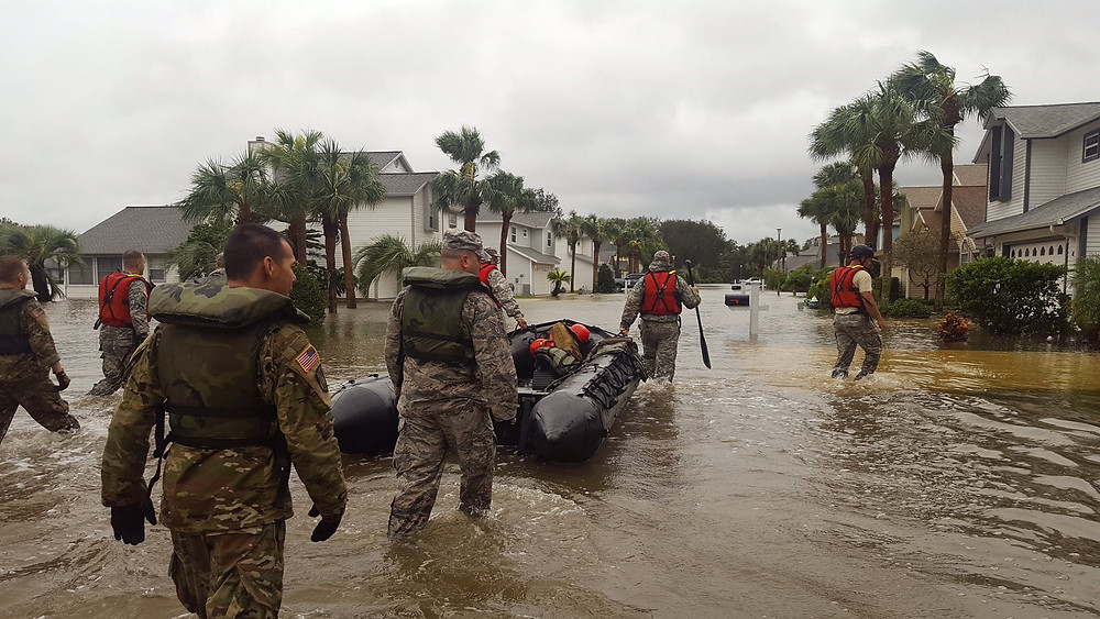 photo of National Guardsmen wading through flood waters with a rescue raft and life jackets.  photo credit army.mil