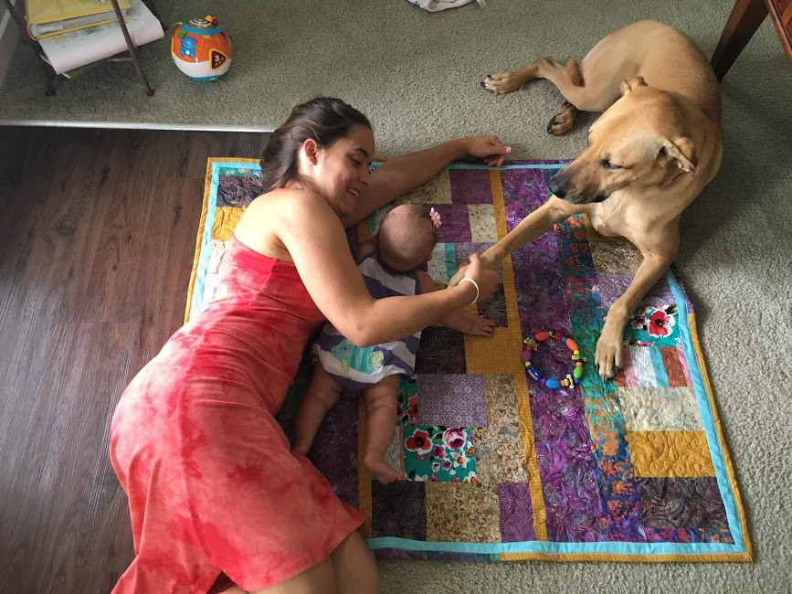 Jenna, baby, and dog on the quilt