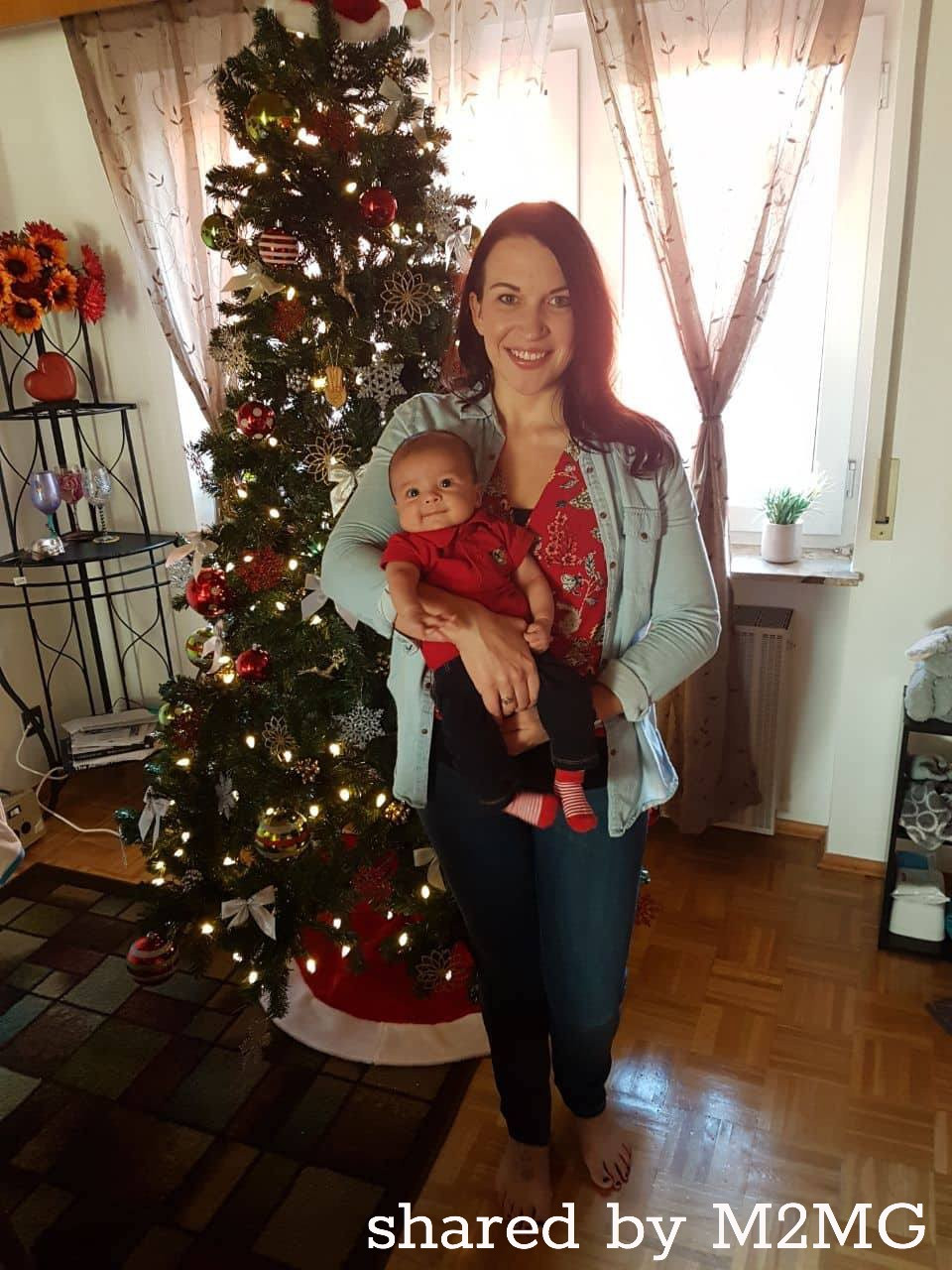 photo of mom and baby by a Christmas tree