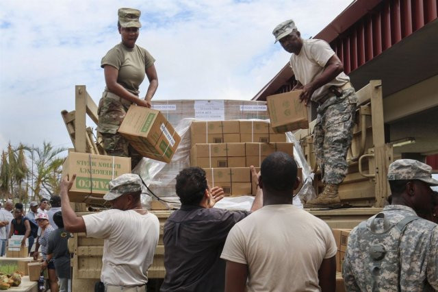 soldiers unload boxes of emergency rations after Hurricane Maria. Photo credit army.mil