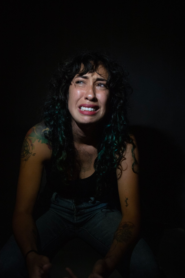 A young woman with long dark hair, crouches down crying
