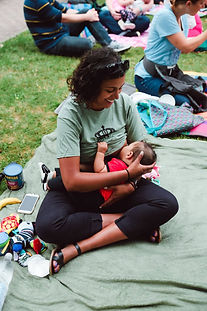 Latin woman breastfeeds her child outside on a blanket