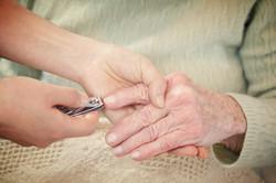 Helping senior woman cutting fingernails_edited