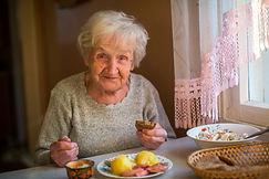 An elderly woman eats at home..jpg