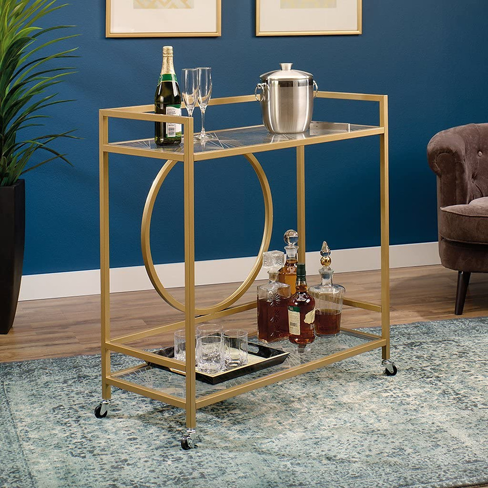 "Sauder International Lux Bar Cart, Glass/Satin Gold - Two, safety-tempered glass shelves features silk-screened geometric pattern Casters for mobility with two locking Finished on all sides for versatile placement Assembled Dimensions - W: 35.591"" x D: 15.748"" x H: 37.205"" Satin Gold Finish. Finish -"