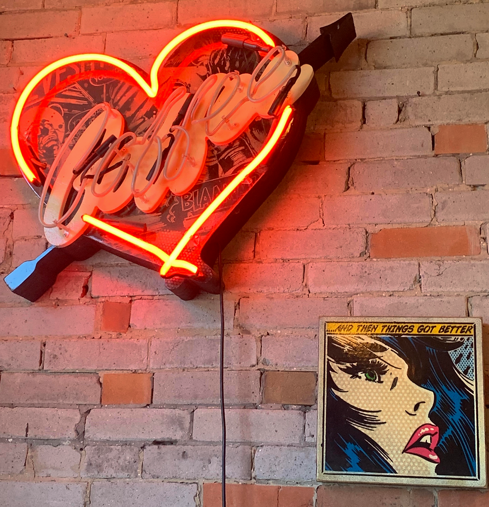 Hula Girl Espresso Boutique neon coffee sign and art prints in coffee shop