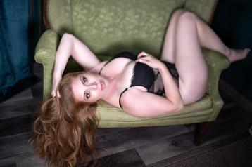 A woman laying down a sofa chair