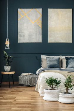 Potted plants in yarn baskets in front of a cozy bed in a dark, navy blue bedroom interior with mode