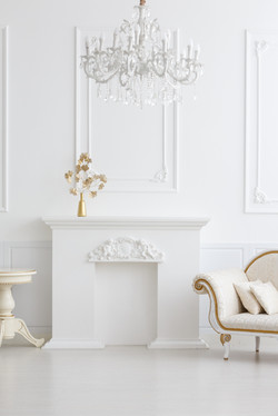 beautiful classical white interior with a fireplace, a sofa and a vintage chandelier. Retro, classic