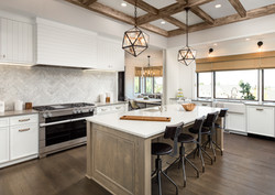 Kitchen Interior with Island, Sink, Cabinets, and Hardwood Floors in New Luxury Home. Features Elega