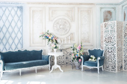 Bright luxury white and blue colored interior living room with flowers in vases. the walls are decor