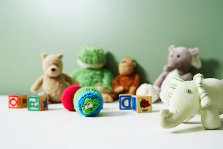 a grouping of childrens toys, a stuffed bear, frog, monkey and 2 elephants can be seen, as weel as ascattering of bright lettered blocks and 2 yarn balls