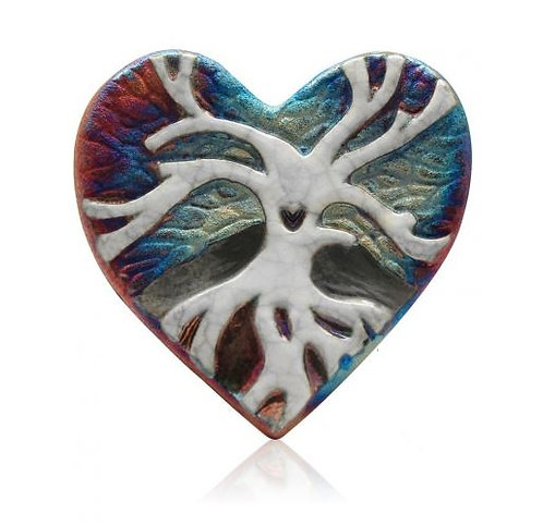Heart shaped pottery with white silhouette of tree of life with heart cut out in trunk of tree,background is blue/prple/coppr