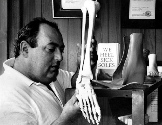 """Stewart holding a skeleton leg, looking at the bones of the feet. In the background it says """"We Heel Sick Soles"""""""