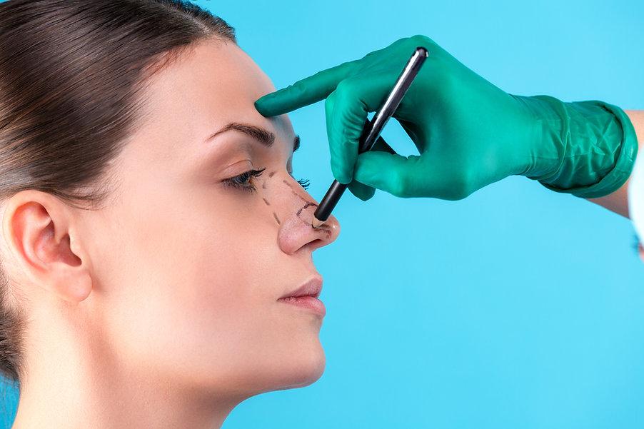 Cosmetic surgeon examining female client