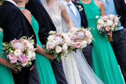 Blush and white summer wedding bouquets of protea, English garden roses, eustoma and eucalyptus foliage at Eton College Chapel