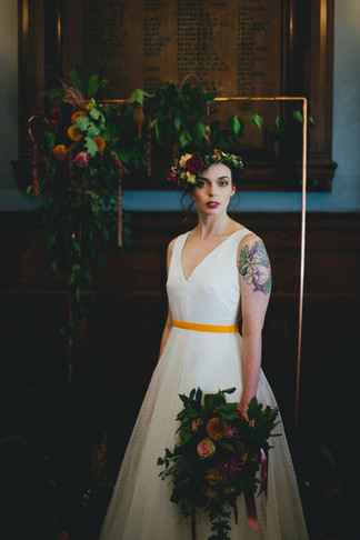 Copper wedding arch with plum and mustard toned blooms
